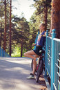 Young woman with bicycle standing on bridge relaxing sexy bike in a country road Stock Image