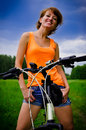 Young woman on a bicycle to the summer field Stock Images