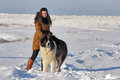 Young woman with a big dog. Sunny winter day Royalty Free Stock Photo