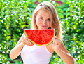 Young woman with big slice watermelon berry fresh in hands smiling face beautiful and blonde hair green nature on background Royalty Free Stock Image