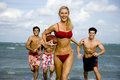 A young woman in a bikini being chased by three men Royalty Free Stock Photo