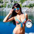 Young woman in bikini holding a clock on a beach. Royalty Free Stock Photo
