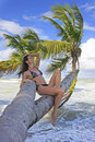 Young woman in bikini sitting on palm trees bonita beach dominican republic Stock Photos