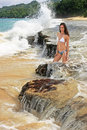Young woman in bikini sitting on rocks at rincon beach samana p peninsula dominican republic Royalty Free Stock Image