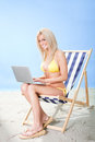 Young woman in bikini using laptop Royalty Free Stock Images