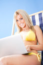 Young woman in bikini using laptop Stock Photo