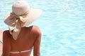 Woman in hat relaxing near pool