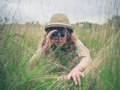 Young woman with binoculars in the grass a wearing a safari hat is hiding tall and is looking through Royalty Free Stock Images