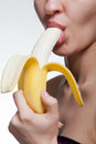 Young woman biting banana on white Royalty Free Stock Photography