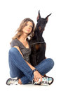 Young woman with black dobermann dog on white Royalty Free Stock Photography