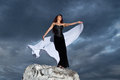 Young woman in a black dress beautiful on background of the cloudy sky Royalty Free Stock Photos
