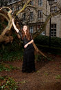 Young woman in a black dress in the park victorian leaning against tree front of house and trunks of trees Royalty Free Stock Images