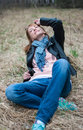Young woman in a black jacket and jeans sitting on the hay Royalty Free Stock Photo