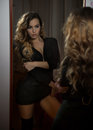 Young woman in black outfit looking into large wall mirror. Beautiful curly fair hair girl posing in front of mirror Royalty Free Stock Photo