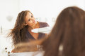Young woman blow drying hair in bathroom modern Royalty Free Stock Images