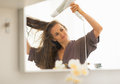 Young woman blow drying hair in bathroom Royalty Free Stock Photo