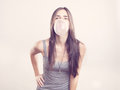 Young woman blowing a bubble gum on pink background Royalty Free Stock Photography