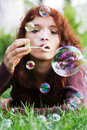 Young woman blowing bubbles. Stock Photos