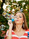 Young woman blowing bubbles cute soap with blurred branches in the background Stock Images