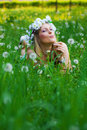 Young woman blowing a dandelion on fields Stock Photos
