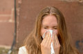 Young woman blowing her nose on a handkerchief conceptual of an illness flu cold allergic rhinitis or hay fever Stock Photo