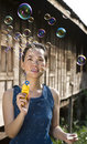 Young woman blowing soap bubbles Stock Image