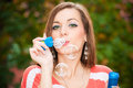 Young woman blowing soap bubbles outdoor portrait of Stock Image