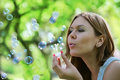 Young woman blows soap bubbles Royalty Free Stock Images