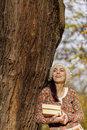 Young woman with books by the tree in the forest Stock Images