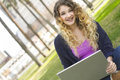 Young woman with braces studying outdoors teenager sitting using a laptop Royalty Free Stock Photos