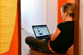 Young woman browses her facebook page on laptop seated on the floor