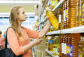 Young woman buys sunflower oil in supermarket Royalty Free Stock Photo