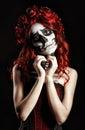 Young woman with calavera makeup (sugar skull) making heart sign Royalty Free Stock Photo
