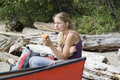 Young woman in a canoe holding a nectarine Royalty Free Stock Photos
