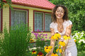 Young woman care of flowers in garden near house Stock Photography