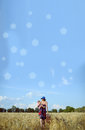 Young woman carrying baby and suitcase in field Royalty Free Stock Photo
