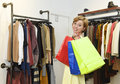 Young woman carrying bags shopping at fashion boutique choosing clothes smiling happy
