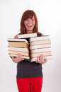 A young woman is carrying a lot of books Stock Photos