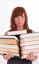 A young woman is carrying a lot of books Royalty Free Stock Photo