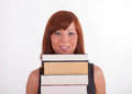 A young woman is carrying a lot of books Royalty Free Stock Photos