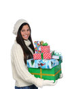 Young woman carrying a stack of christmas presents profile shot large the is looking towards the viewer and smiling Royalty Free Stock Photos