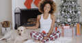 Young woman celebrating christmas with her dog attractive trendy african sitting in front of the decorated fireplace and tree Stock Photos