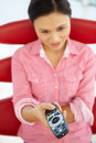 Young woman on chair with remote control Royalty Free Stock Photos