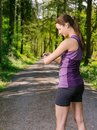 Young woman checking her running time photo of a on a jogging path through a forest Royalty Free Stock Photography