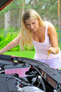 Young woman checking oil level in the car Stock Image