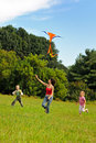 Young woman and children flying a kite Royalty Free Stock Image