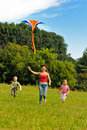 Young woman and children flying a kite Stock Photo