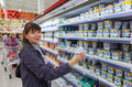 Young woman choosing fresh milk produces samara russia september at shopping in dairy supermarket store magnit russia s largest Royalty Free Stock Photo