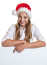 Young woman with christmas hat pointing on a signboard laughing long blond hair and at white background Royalty Free Stock Images