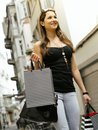 Young woman in the city shopping photo of a beautiful walking through holding bags Stock Photos